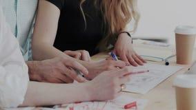 雇员谈论一个建筑项目 接近的吃食物女孩射击 创造性的室内设计师桌面有图纸的和 股票录像