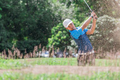 雍亚洲高尔夫球运动员爆炸沙子 免版税库存照片
