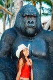 雍美丽的亚裔女孩坐大猴子雕象 免版税库存图片