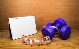 雏型模转台与测量的磁带健身哑铃的日历页 免版税库存图片