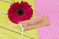 雏菊有礼物标记的大丁草开花与德国词, Auszeit,手段暂停或放松 免版税库存图片