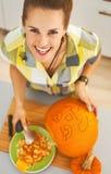 雕刻一个大橙色南瓜杰克O灯笼的愉快的妇女 库存图片