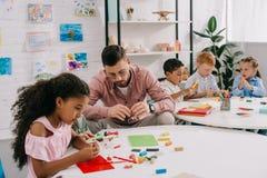 雕刻与五颜六色的彩色塑泥的老师和不同种族的孩子图在桌上 免版税库存照片