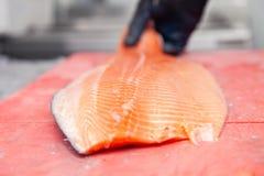 雕刻与刀子的厨师厨师整个新鲜的挪威三文鱼鱼在红色切板在餐馆专业厨房里, 库存照片