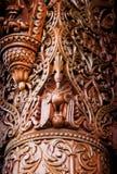 雕刻列的亚洲印第安棕色木鸟 库存图片