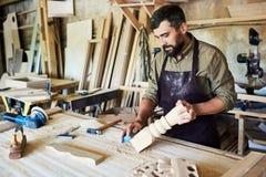 雕刻台阶岗位的有胡子的木匠在商店 图库摄影