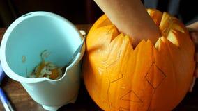 雕刻和绘一个南瓜的年轻男孩为在桌上的万圣夜 库存照片