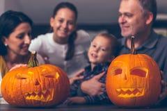 雕刻大橙色南瓜的家庭为万圣夜 图库摄影