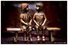 雕刻小男孩和女孩坐一条长凳本质上 免版税库存照片