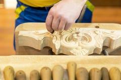 雕刻木头的雕刻师的手 库存照片