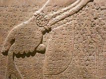 雕刻楔形文字的墙壁的古老亚述人 库存照片