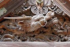 雕刻神圣的龙头的古老日本木头在高野山 免版税库存照片