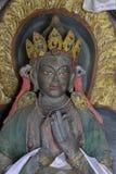 雕刻菩萨,西藏老师Naropa,灰色颜色雕象在色的衣裳和金黄冠的 库存照片