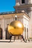 """雕塑""""Sphaera"""" -站立在K的金黄球的一个人 免版税库存图片"""