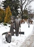 雕塑在市里加 一个古铜色人和夫人有中国咸菜狗的 图库摄影
