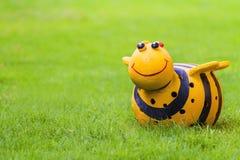 雕塑在绿草领域的蜂玩偶 库存图片