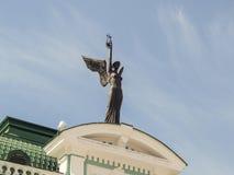 雕塑飞过了在鄂木斯克状态学术戏曲剧院的主要门面的前面的天才 免版税库存照片