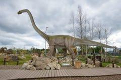 雕塑食草恐龙马门溪龙多云在天之前 古生物学儿童` s公园 免版税库存照片