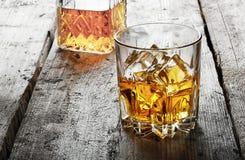 雕琢平面的杯与冰和蒸馏瓶的威士忌酒 免版税库存照片