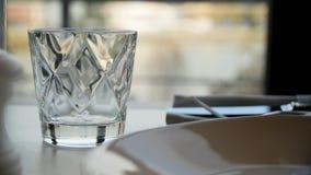 雕琢平面的杯在自然背景的水 清除雕琢平面的玻璃用在一张黑暗的木桌上的威士忌酒,特写镜头 空 免版税库存图片