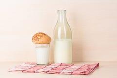 雕琢平面的杯牛奶用对此的一个小圆面包在一个红色被摆正的洗碗布近被打开的古板的瓶站立牛奶 免版税图库摄影
