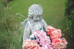 雕象天使和花在庭院里 库存图片