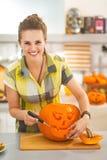 雕刻一个大橙色南瓜杰克O灯笼的主妇在厨房里 图库摄影
