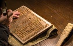 雕刻一个木打印块的工匠 库存图片