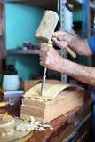 雕刻与凿子和锤子的家具工的手木头 库存照片