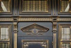 雕刻与在门上的曲拱的木头在一个老大厦 免版税库存图片