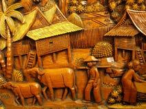 雕刻关于泰国传统农夫的木头 库存照片