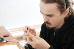 雕刻家做手工制造微型塑料玩具,房子装饰技巧爱好,装饰创作的艺术家人 免版税库存图片
