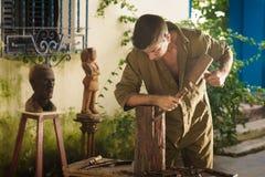 年轻雕刻家艺术家运作的和雕刻的木雕象 免版税库存照片