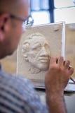 雕刻家雕刻人` s面孔的雕塑 水平的框架 免版税库存照片