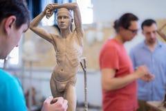 雕刻家雕刻从自然的一个人` s雕塑 水平的框架 库存照片