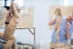 雕刻家雕刻从自然的一个人` s雕塑 水平的框架 免版税库存图片