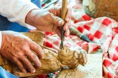 雕刻木头的雕刻师的手 免版税库存照片
