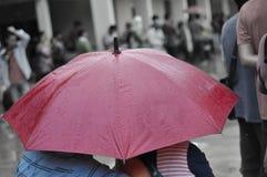 雨和红色伞 免版税图库摄影