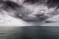 雨和风雨如磐的云彩在海 免版税库存图片