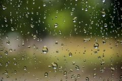 雨在与阳光的车窗,湿玻璃,下雨天落下 免版税库存照片