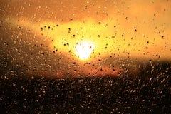 雨在日落背景的窗口外 在玻璃的水下落在下雨期间 库存图片