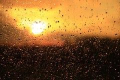 雨在日落背景的窗口外 在玻璃的水下落在下雨期间 库存照片