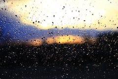 雨在日落背景的窗口外 在玻璃的水下落在下雨期间 免版税库存照片