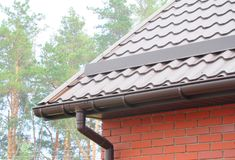 雨天沟管道系统设施 屋顶建筑 下雨天沟系统和屋顶保护免受雪雪卫兵 免版税库存照片