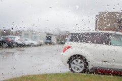 雨天,雨背景 模糊的汽车剪影 在视窗的雨下落 免版税库存图片