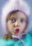 雨天-一个小女孩的面孔在一个满地露水的窗口后的 免版税图库摄影