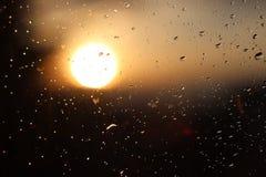雨宏观摄影在落日的模糊的背景的玻璃下降 在黑暗和橙色口气的纹理 免版税库存图片