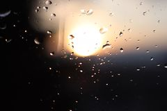 雨宏观摄影在落日的模糊的背景的玻璃下降 在黑暗和橙色口气的纹理 库存照片