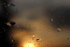 雨宏观摄影在落日的模糊的背景的玻璃下降 在黑暗和橙色口气的纹理 免版税库存照片