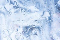 雨小滴 溢出的水在玻璃,自然蓝色背景滴下 免版税库存照片